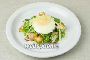 Салат распределить по тарелкам, полить заправкой и на каждую порцию выложить яйца-пашот. Сверху посыпать сыром и немедленно подавать к столу.