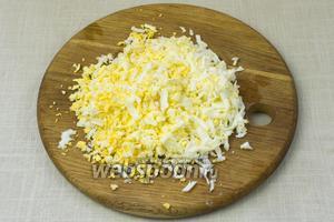 Яйца отварить вкрутую, приблизительно 7 минут с момента закипания и натереть на крупную тёрку.