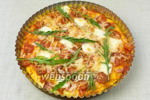 Готовую пиццу посыпать мытыми листочками рукколы и сразу подавать.