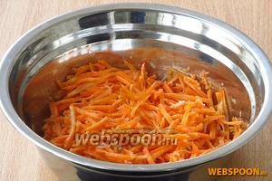 Выложить морковь в миску, посолить, посыпать перцем (красным и чёрным), растертым чесноком и заправить уксусом по вкусу. Всё перемешать, помять руками до мягкости, плотно закрыть крышкой и оставить на 30 минут.