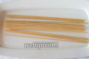 Замочить деревянные шпажки в холодной воде. Длина шпажек должна равняться диаметру вашей сковороды.