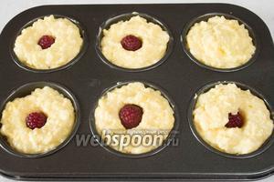 Подготовить форму, смазать сливочным маслом. Заполнить творожной массой ячейки. Вставить внутрь ягоду малины. Закрыть её творожной массой. Поставить в горячую духовку. Выпекать 30 минут при температуре 180 °С.
