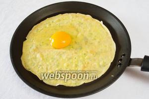 Разбить яйцо и очень осторожно поместить его на одну половину, сразу закрыть второй половиной.