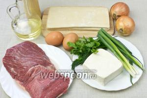 Для такого пирога понадобятся: говядина, брынза, готовое слоёное тесто, яйца, лук репчатый, зелень, оливковое масло.
