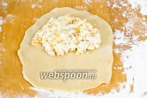 Из каждого шарика раскатываем овал. Необходимо раскатывать от центра к краям, тогда пирожки не порвутся в процессе жарки. И выкладываем начинку.