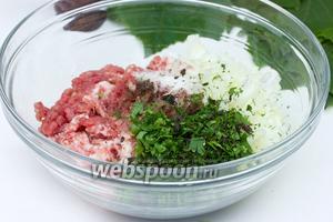 Измельчить всю зелень — базилик, петрушку, укроп и мяту. Добавить вместе с нарезанным луком в свиной фарш.
