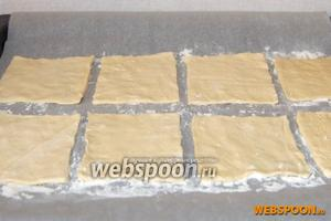 Разрезать тесто на квадраты. Половину из них выложить на противень с пергаментом, присыпанным мукой.