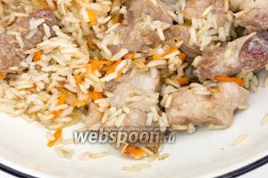 Смешать рис с обжаренным мясом и овощами.