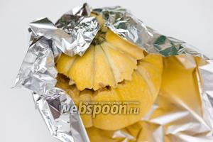 Положить на верх сметану, накрыть крышечкой (верхушка от тыквы) и завернуть плотно в фольгу. Запекать около 40 минут при 200 °C.