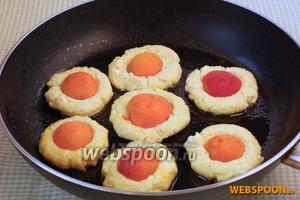 На сковороде раскалить 1 ст. л. растительного масла. Ложкой выложить небольшие лепёшки. Сверху — половинки абрикос.