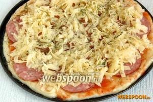 Посыпаем орегано (это крайне обязательная пряность, она придает тот особый вкус и аромат пицце). Выкладываем сервелат, посыпаем сыром и сушёным укропом.