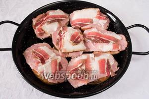Накрыть картофелины полосками бекона. Выложить их на противень или сковороду. Поставить в горячую духовку. Запекать при температуре 200 °С в течение 20 минут.
