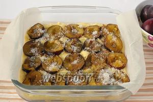 Сверху на тесто выложить половинки слив разрезом вверх. Посыпать смесью из 2 ложек корицы и 2 ложек сахара.