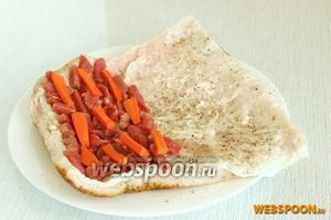 Сало нужно посолить и приправить смесью перцев. Далее на одну половинку пласта сала выложить мелко нарезанное мясо, сверху положить брусочки моркови.