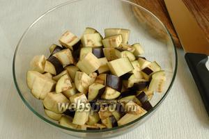 Баклажаны следует промыть, удалить плодоножки и кончики, то есть срезать с двух сторон. Нарезать кубиками со стороной примерно 1,5-2 см.