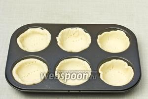Тесто раскатать и заполнить формочки, формируя корзинки. Проколоть тесто в нескольких местах и поставить в разогретую до 180 °С духовку на 15-20 минут, пока корзинки не станут золотистого цвета. Затем их вынуть и остудить.