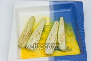 Отдельно вилкой смешиваем сырые яйца, слегка присолив. Ломтики баклажан окунаем в яичную смесь.
