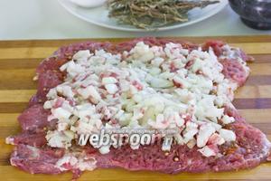Выкладываем начинку, распределяем её по всему периметру мясного пласта, оставляя место от краёв.