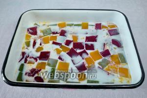 Залить цветные кубики желе 200 мл молока с разведённым в нём желатином. Поставить в холодильник на 3 часа.