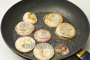 Разогреть сковороду, добавить оливковое масло и обжарить кружочки лука по 3 минуты с каждой стороны. Затем посыпать из солью, тимьяном и сахаром. Подержать ещё 1 минуту и снимать с огня. Переворачивать лук удобнее всего кулинарными щипцами.