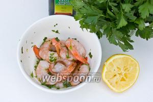Размороженные крупные креветки положить в глубокую миску, добавить измельчённую петрушку и зубчик чеснока, соль, оливковое масло и сок половины лимона. Оставить так мариноваться минут 15.