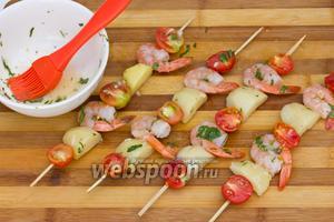 Щедро смазать шашлычки оставшимся после маринования креветок маринадом.