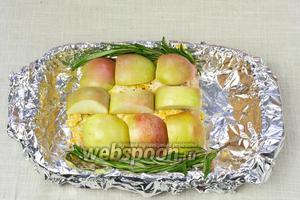 Мясо обложить яблоками и веточками розмарина.