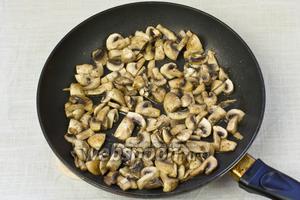 Разогреть сковороду, добавить растительное масло и выложить шампиньоны. Жарить до тех пор, пока они не потемнеют и не испарится вся влага.