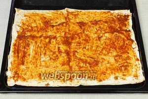 Выложить лист лаваша на противень и смазать томатным соусом. Затем выложить второй лист поверх первого, смазать соусом.