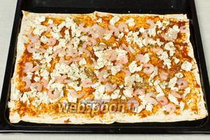 Выложить размороженные креветки и посыпать сверху орегано, сухим укропом, чёрным перцем. Взбрызнуть оливковым маслом и поставить в разогретую до 180 °C духовку на 10 минут.
