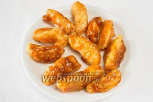 Выкладывать готовые дольки яблок в карамели на тарелку, смазанную маслом. Подавать на десерт.