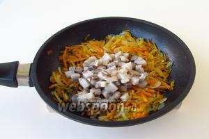 В горячую морковно-луковую массу выложить кусочки сельди, слегка посолить и поперчить.