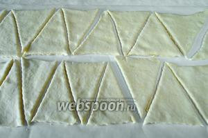 Утром холодное тесто раскатать в тонкий пласт. Разделить его на полоски. Нарезать длинные треугольники.
