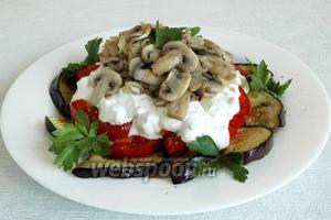 Собираем салат: сначала слой баклажан, затем — помидоры, нарезанные кружочками или полукругами. Поперчить смесью перцев, после — слой соуса и сверху — грибы с луком. Украсить свежей зеленью.