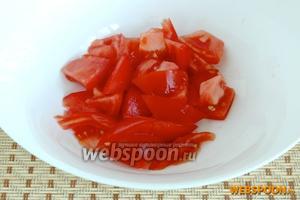 В большой салатник выложить чистый и нарезанный дольками помидор.
