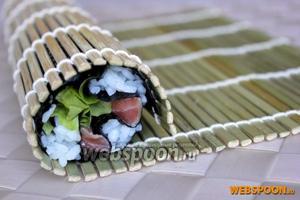 Сверните ролл — кусочки рыбы обернутся в нори, а листья салата соединятся между собой. Зафиксируйте ролл макисой.