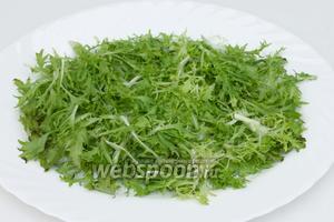Готовим заправку: для этого смешиваем венчиком горчицу, лимонный сок, два сырых желтка, оливковое масло, измельчённый чеснок, соль и чёрный молотый перец до получения однородного соуса. Собираем салат: выкладываем помытые и обсушенные листики салата фризе на плоское блюдо первым слоем (3/4 от всего объёма салатных листьев, остальные пойдут на последный слой).