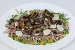 Луково-чечевичный слой слегка поливаем приготовленным горчичным соусом, используя около 1/3 всей заправки. Далее выкладываем 2/3 всей ветчины, половинки яиц, обжаренные и полностью остывшие грибы.