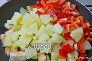Добавляем к курице ананасы, нарезанный перец, молотый имбирь, мёд, соевый соус, солим перчим и обжариваем 10-15 минут на среднем огне.