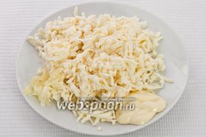 Добавляем в натёртый сыр майонез, измельчённый чеснок и перемешиваем.