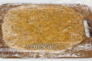Раскатать тесто между двумя листами пергаментной бумаги или пищевой плёнки.