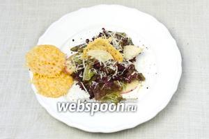 На тарелку выложить листья салата с яблоками. Посыпать оставшимся тёртым пармезаном и украсить сырными сеточками. В таком виде подавать.