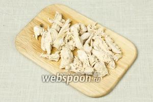 Курицу отварить до готовности (приблизительно 30 минут). Остудить и нарезать вдоль волокон.