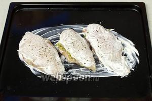 Противень смазать сметаной и выложить куриные грудки. Их также смазать сметаной и посыпать свежемолотым чёрным перцем. Противень поставить в разогретую до 190 °С духовку на 30-40 минут.