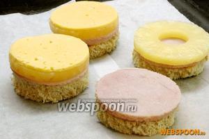 Выложить хлеб на противень, застеленный пергаментной бумагой. Сверху выложить кружочки ветчины, также выдавленные стаканом, колечки ананасов и выдавленный кружочек сыра.