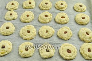 Сформовать плоские шарики (мокрыми руками). Окунуть в сахар верхнюю часть печенья и разложить их на бумагу для выпечки на противень. Украсить изюмом.