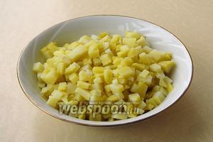 Картофель тщательно вымыть, выложить в кастрюлю, залить горячей подсоленной водой и отварить до мягкости, а затем остудить, очистить и нарезать мелкими кубиками.