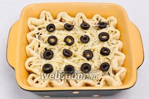 Сверху обильно присыпать сыром и украсить маслинами.