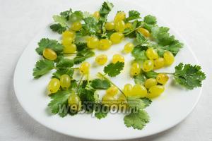 На блюдо выложить зелень кинзы или листья салата и виноград. Взбрызнуть оливковым маслом, соком лимона, поперчить, посолить.
