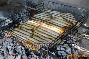 Закрепите (зафиксируйте) куриные окорочка в решётке для гриля и готовьте их над углями.